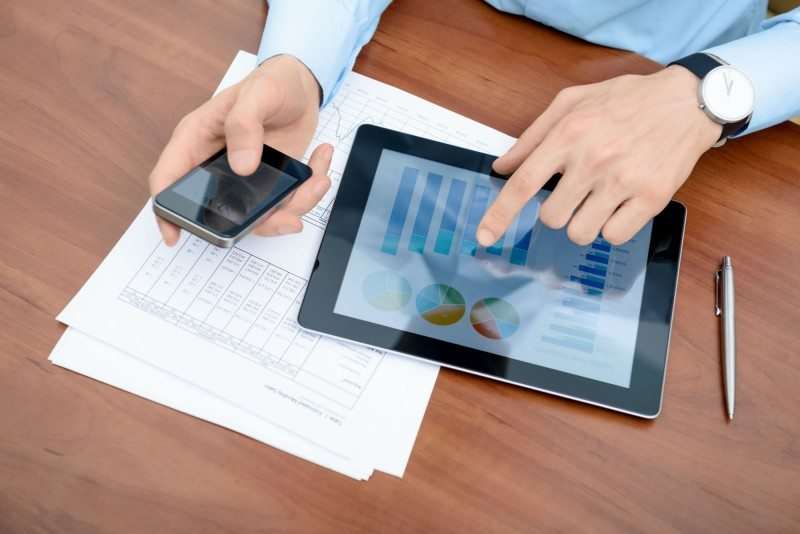 Foto de duas mãos masculinas, uma segurando um celular, e outra mexendo em um tablet, representando as ferramentas para gestão
