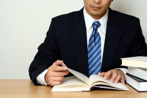 Foto de um homem com roupas sociais lendo um livro