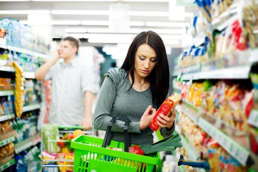Foto de uma mulher fazendo compras no supermercado e um homem desfocado ao fundo falando ao telefone