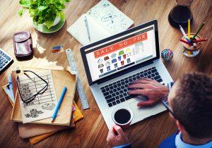 Foto de um homem mexendo no computador e tomando café, representando uma estratégia de marketing