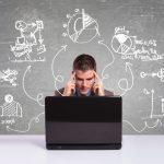 Imagem de um homem com dois dedos na cabeça em frente a um computador, e diversos gráficos a sua volta