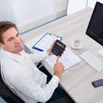 Foto de um rapaz sentado em uma mesa com uma calculadora em mãos, representando como escolher um contador