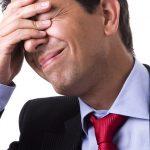 Foto de um empresário com a mão na testa e expressão de insatisfação, representando os erros de empreendedores