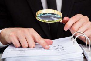 Foto de um homem mexendo em documentos e olhando com lupa, representando o momento de regularizar sua empresa