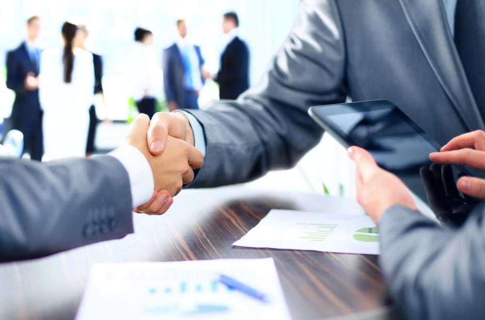Imagem de dois homens apertando as mãos