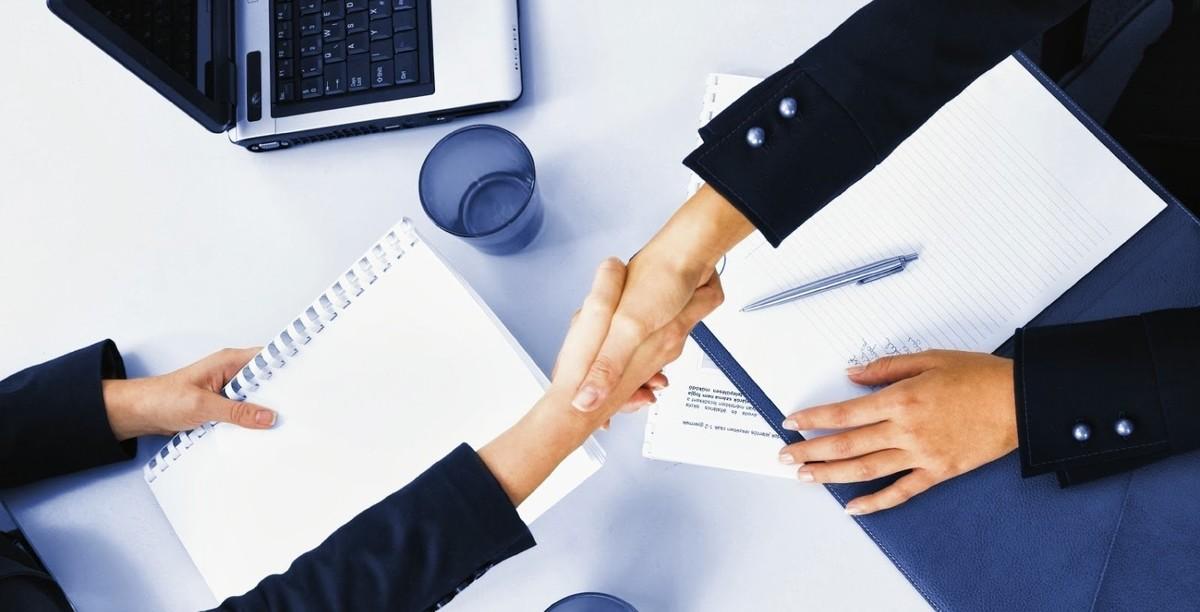 Duas pessoas apertando as mãos, representando abrir uma empresa