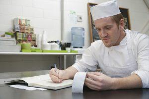 Homem cozinheiro anotando coisas em um papel, representando a contabilidade para pequenas empresas