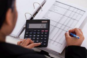 Foto de uma pessoa usando uma calculadora e anotando em um papel, representando contratar um contador