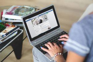 Pessoa mexendo em um notebook com o facebook aberto, representando uma das dicas de marketing