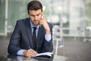 Empresário pensando e anotando, representando as principais dúvidas sobre abertura de empresas