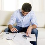 Foto de um homem fazendo contas sentado, representando o nome negativado