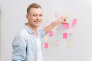 Foto de um rapaz sorrindo enquanto prende alguns papeis na parede