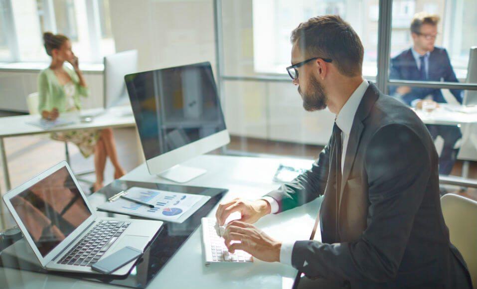 Foto de um rapaz digitando em um notebook e visualizando em uma tela de computador