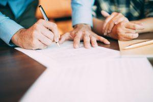 Mão de um homem assinando papeis, representando a abertura de empresa própria