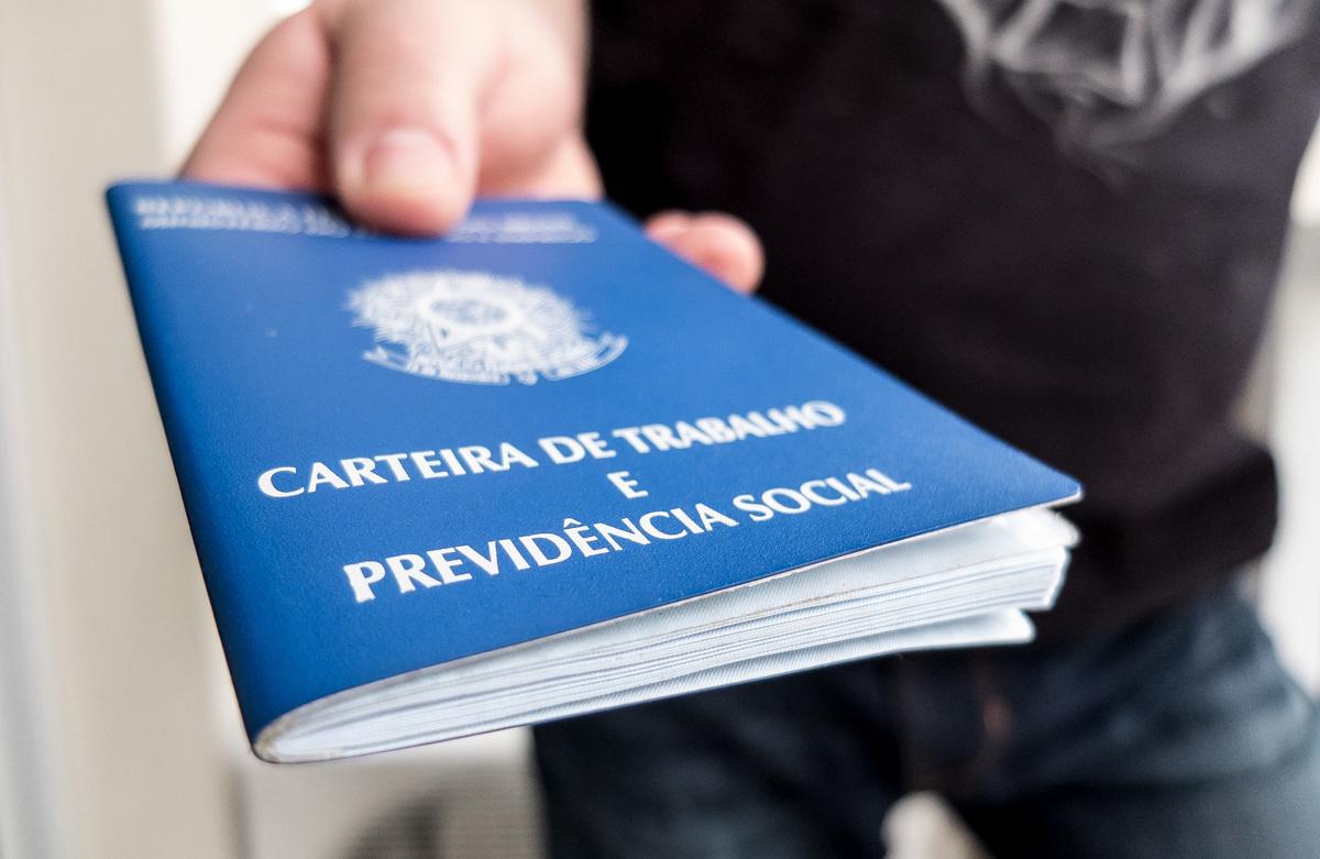 Foto de uma pessoa apresentando a carteira de trabalho, representando o cálculo de FGTS