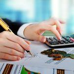 Foto de uma mão feminina anotando em um papel as contas que faz em uma calculadora, representando o financiamento com consultoria jurídica