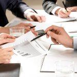 Imagem de algumas pessoas em uma mesa em uma reunião formal