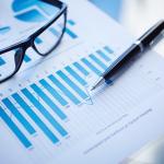 Foto de uma caneta e um óculos por cima de uma folha com alguns gráficos impressos
