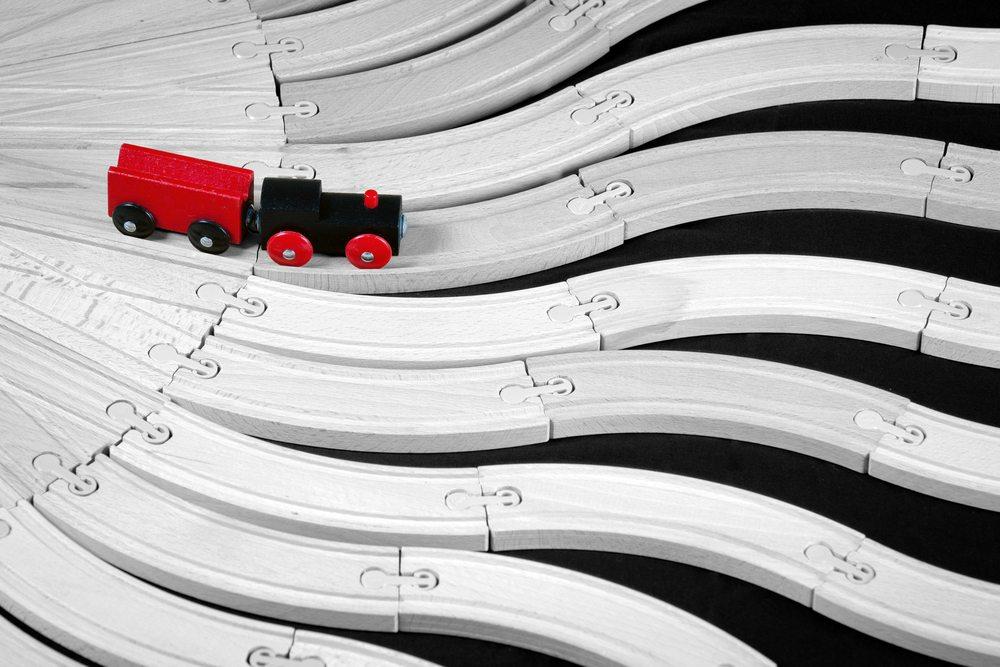 Imagem de um trem de brinquedo com trilhos em diversos caminhos diferentes