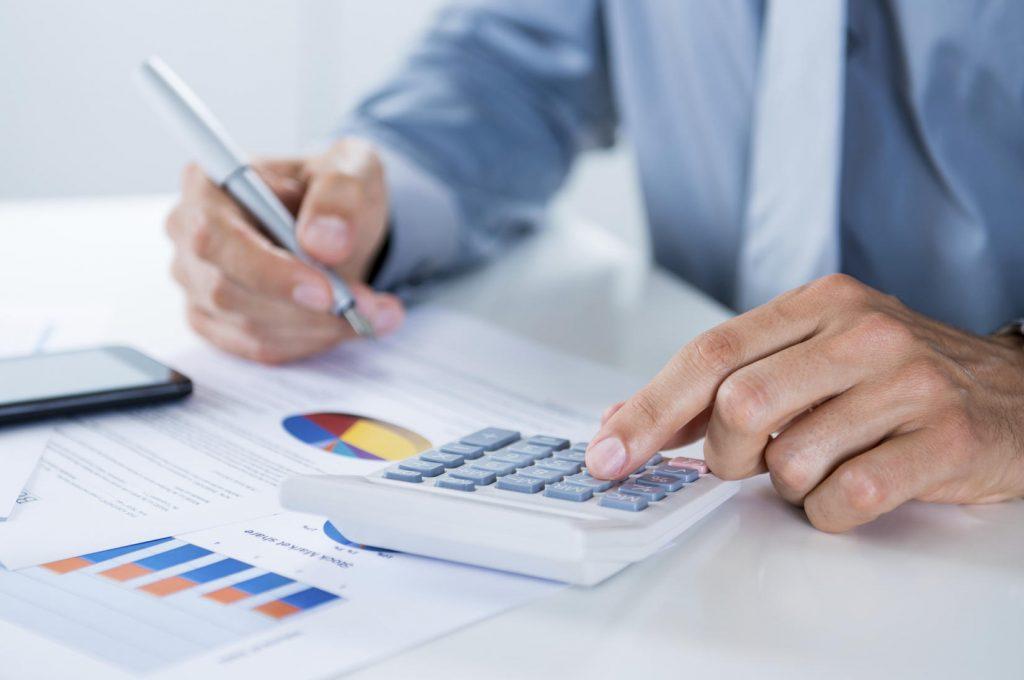 Mão masculina digitando em uma calculadora, representando a Simples Nacional 2016