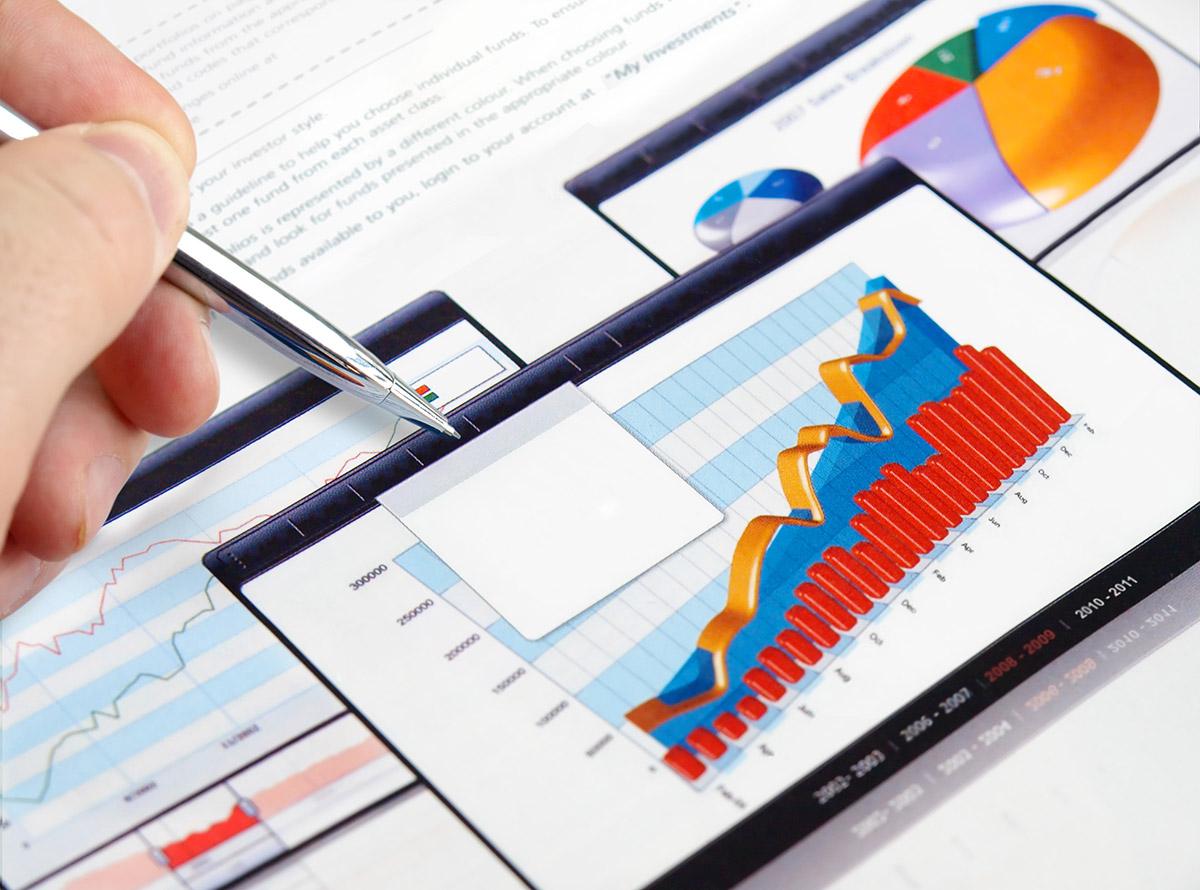 Foto de uma mao masculina segurando uma caneta e alguns gráficos por baixo