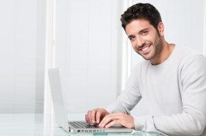 Foto de um homem sorrindo e mexendo em um notebook. retirando seu certificado digital