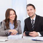 Um casal fazendo contas e anotando em um celular, representando um escritório de contabilidade na mesma cidade