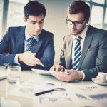 Dois homens conversando e analisando um papel sobre abrir a sua empresa