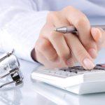 Mão feminina digitando em uma calculadora e segurando uma caneta, com um óculos ao lado