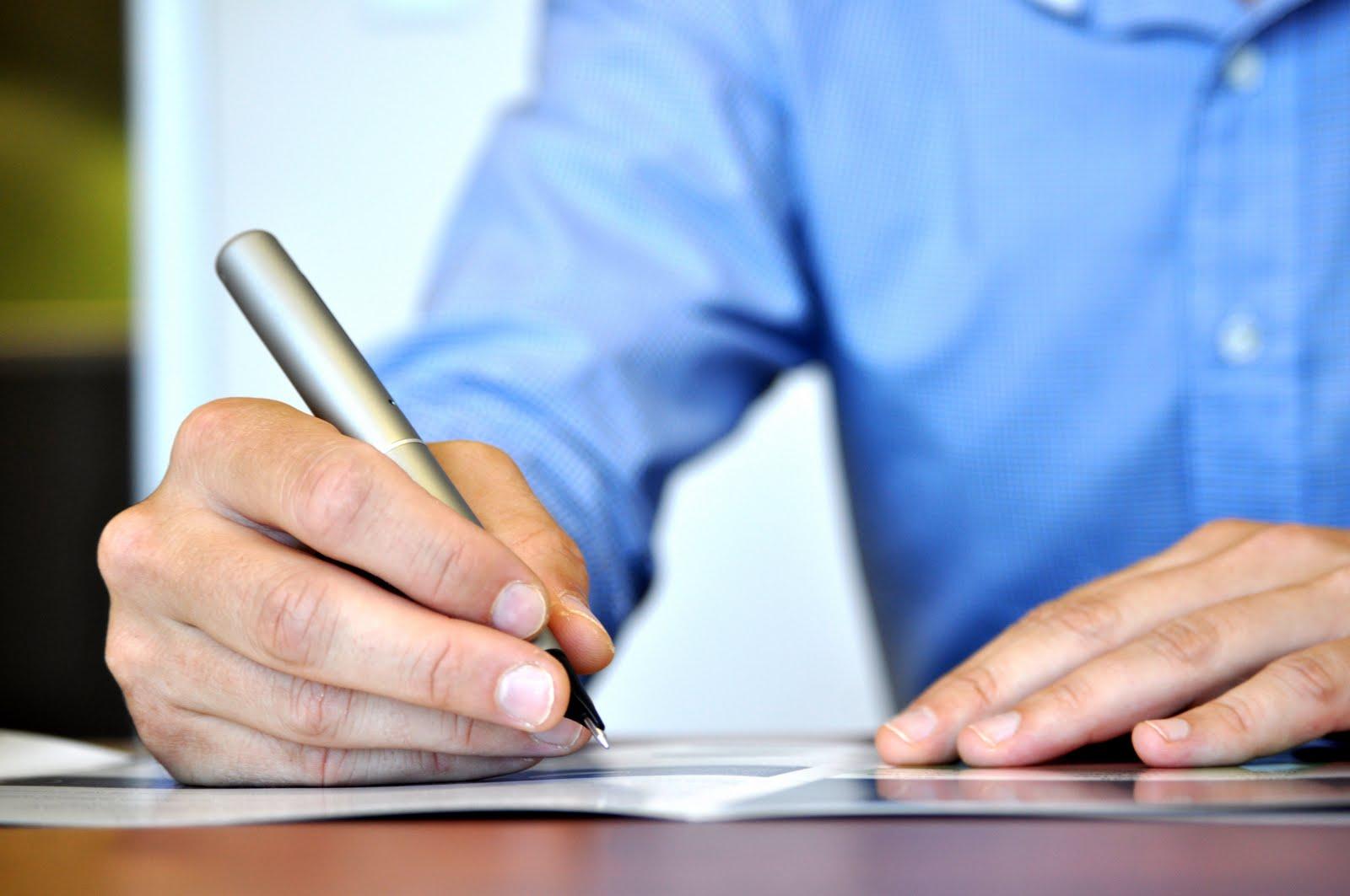 Mão de um homem escrevendo com uma caneta