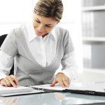 Foto de uma mulher formal checando um caderno com um notebook ao lado