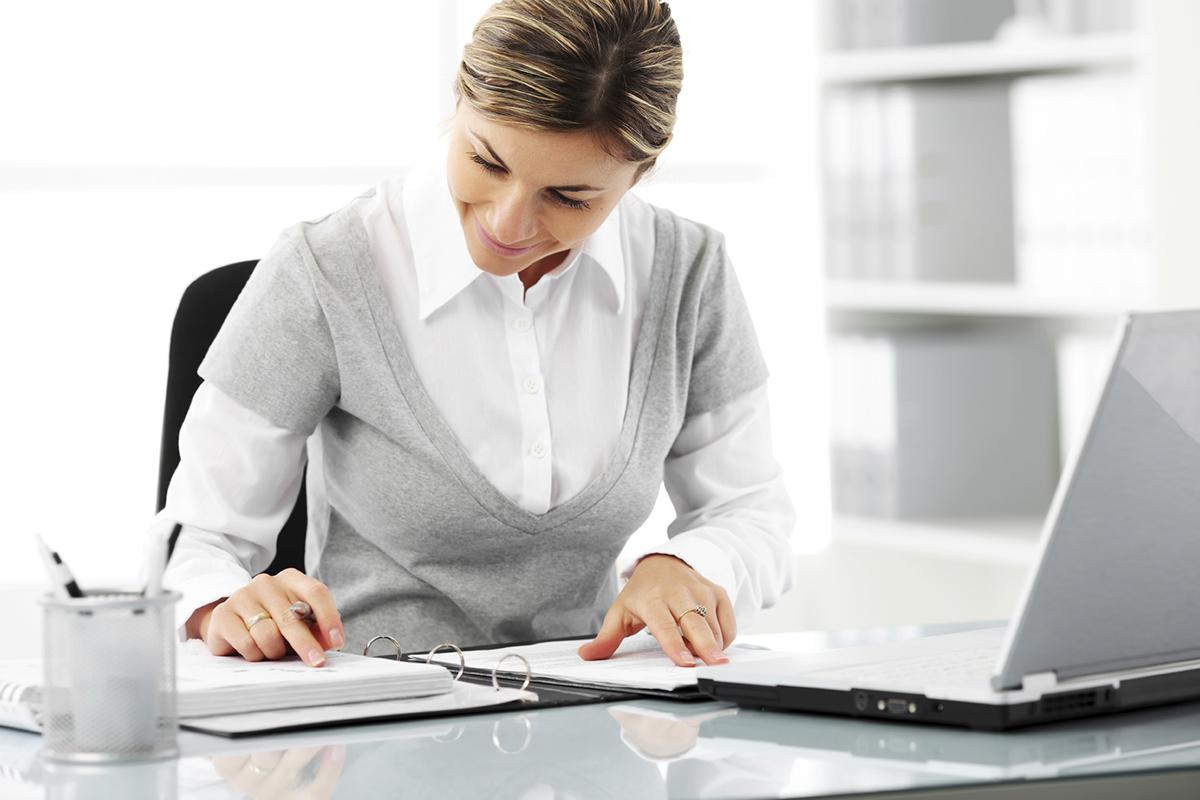 Foto de uma mulher formal checando um caderno com um notebook ao lado, representando como obter um cnpj