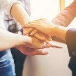 Foto de várias mãos unidas em equipe, representando a missão das empresas