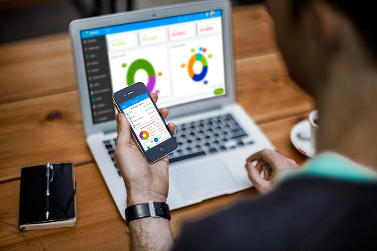 Foto com um homem mexendo em um celular e um notebook, ambos abertos no aplicativo Mobills