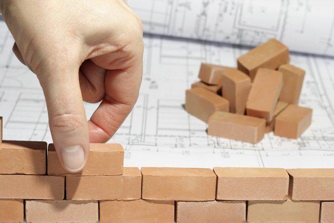 Foto de uma mão montando uma parede com pequenos blocos, representando o planejamento a longo prazo