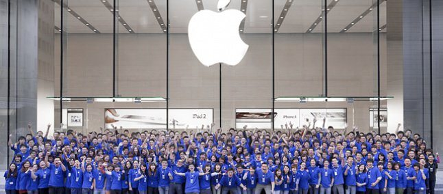 Foto de vários funcionários da Apple reunidos abaixo do logo da empresa, representando as estratégias de endomarketing utilizadas por ela