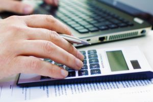 Foto de uma mão masculina digitando em um computador e fazendo conta de finanças pessoais em uma calculadora