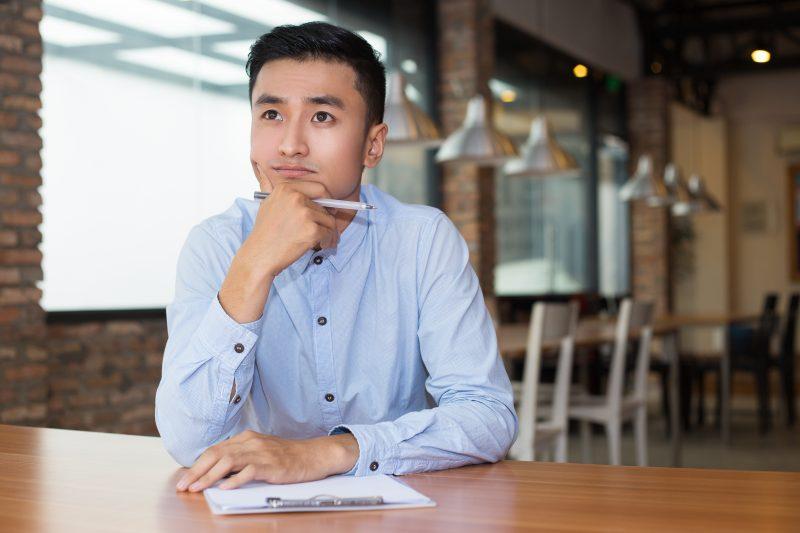 Homem com a mão no queixo, representando o perfil do empreendedor de sucesso