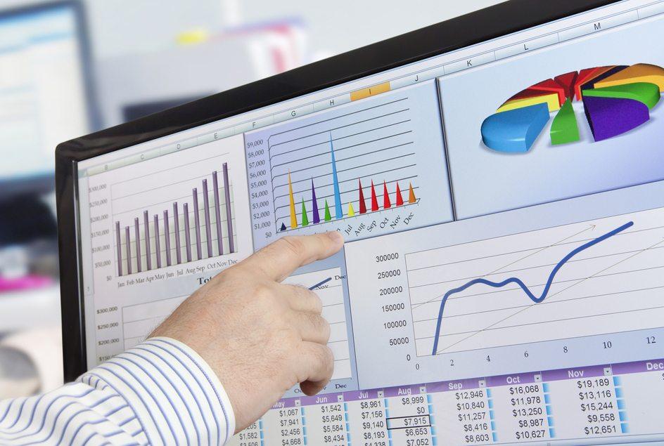 Foto de um rapaz apontando para a tela de um computador, analisando pesquisa de mercado