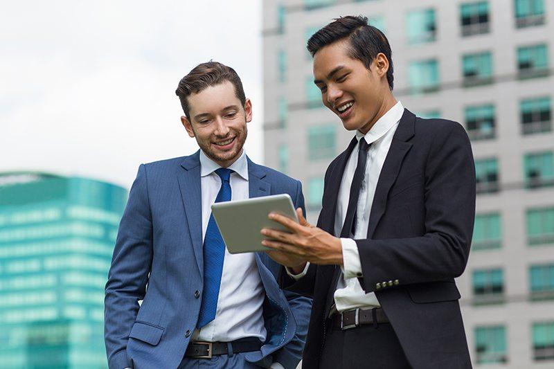 Dois homens vestidos com terno mexendo em um tablet, representando o pagamento do boleto do MEI online