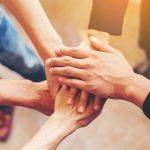 Foto de muitas mãos juntas, representando o empreendedorismo social