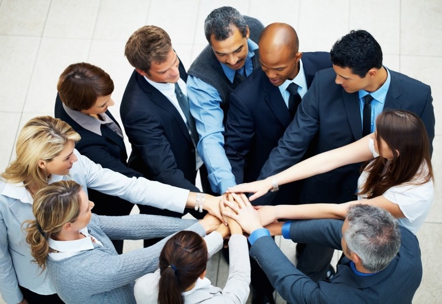 Foto de muitas pessoas com as mãos juntas, representando a gestão de pessoas nas PMEs