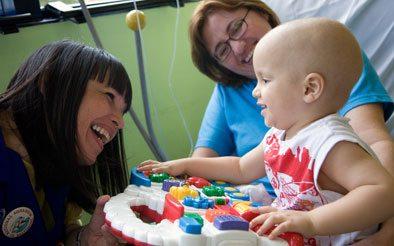 Foto de uma criança com duas mulheres do Graacc