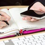 Foto de uma mão anotando em uma agenda para empreendedores e um celular na outra mão