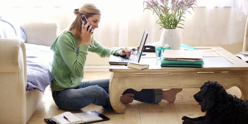 Mulher sentada em uma mesa de casa e falando ao telefone, representando a franquia home based