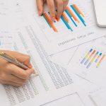 mão feminina mexendo em alguns papeis representando o que é DRE na contabilidade