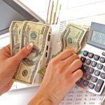 Foto de uma pessoa contando dinheiro com uma calculadora ao lado, representando a diferença entre faturamento e lucro