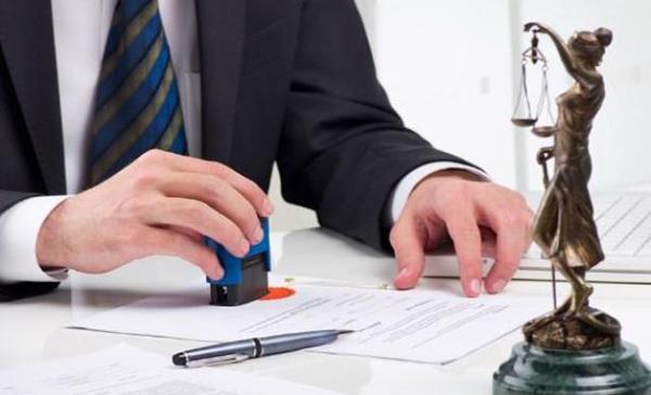 Foto de uma mão masculina carimbando em alguns papeis, representando legalizar sua empresa