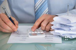 Foto de um homem escrevendo em um papel e digitando em calculadora, representando as obrigações fiscais