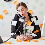 Foto de uma mulher falando ao telefone com muitos papeis colados nela e na parede atrás, como melhorar a produtividade